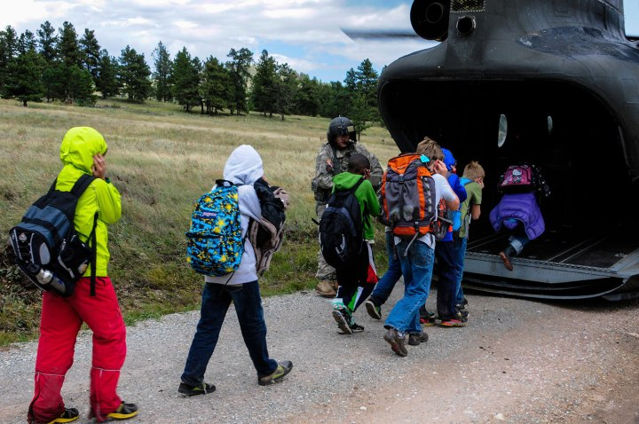 Handout photo of children from Cal-Wood Education Center in Jamestown, Colorado boarding rescue helicopter after severe flooding shut down major roads leading out of town