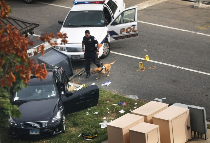 A police officer checks out a car on grass with his canine near the U.S. Capitol October 3, 2013 on Capitol Hill in Washington.