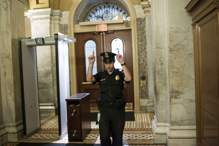 A Capitol Police Officer directs people away from a door on Capitol Hill October 3, 2013 in Washington.