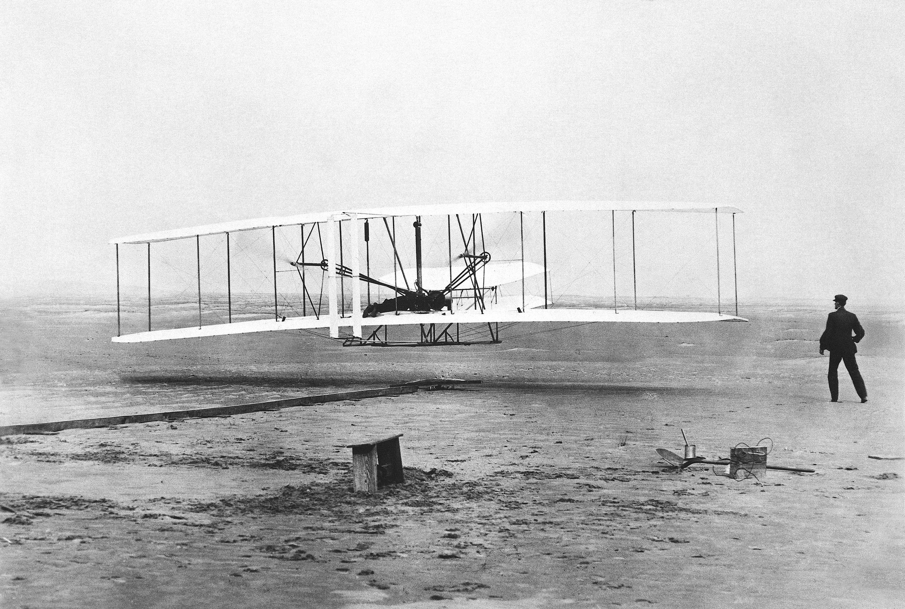 "Orville Wright is at the controls of the ""Wright Flyer"" as his brother Wilbur Wright looks on during the plane's first flight at Kitty Hawk, N.C. Dec. 17, 1903."