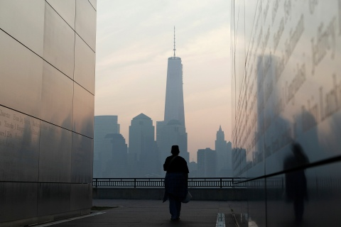 A woman looks out at New York's Lower Manhattan and One World Trade Center from inside 9/11 Empty Sky memorial at Liberty State Park in Jersey City