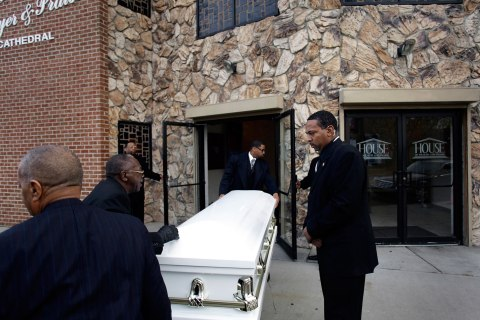 The casket for shooting victim Renisha McBride is removed from a hearse before her funeral service in Detroit