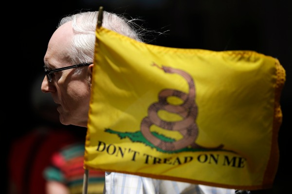 Bernie Brunner, of Springfield, Pa., holds a flag during a tea party rally protesting extra IRS scrutiny of their groups, May 21, 2013, in Philadelphia.