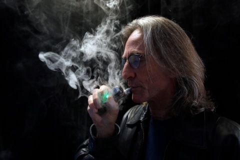 John Hartigan, proprietor of Vapeology LA, a store selling electronic cigarettes and related items, takes a puff of an electronic cigarette at his store in Los Angeles on Dec. 4, 2013.