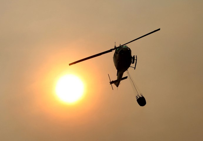 A California Fire helicopter flies over Pfeiffer Ridge on Dec. 16, 2013, in Big Sur, Calif.