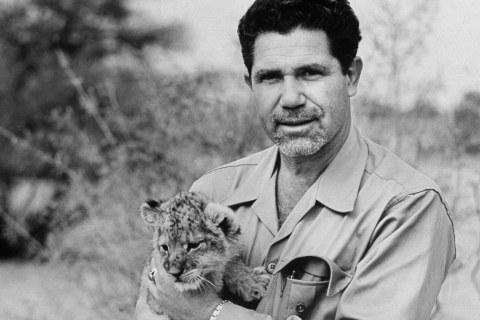 LIFE photographer John Dominis holds a lion cub.