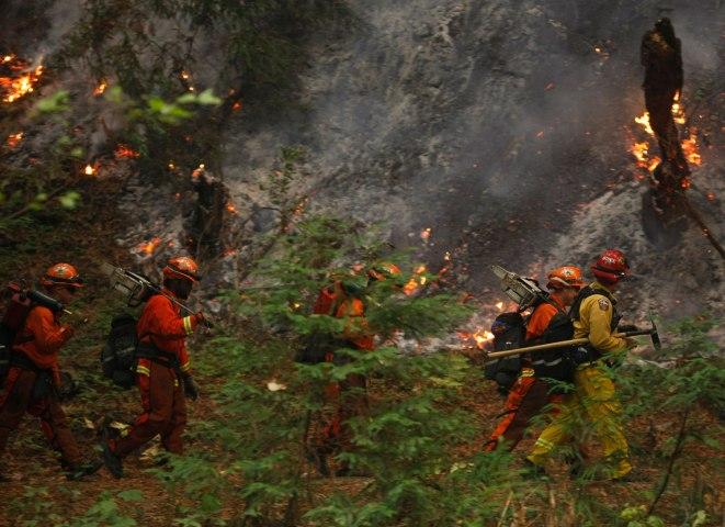 A firefighting crew walks past burning trees in Big Sur, California, on Dec. 16, 2013.