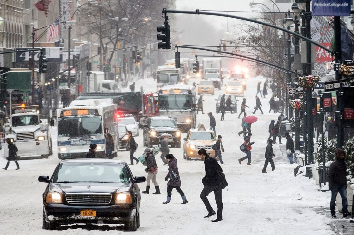 Pedestrians brave wind and snow as they cross Fifth Avenue, Jan. 3, 2014, in New York.