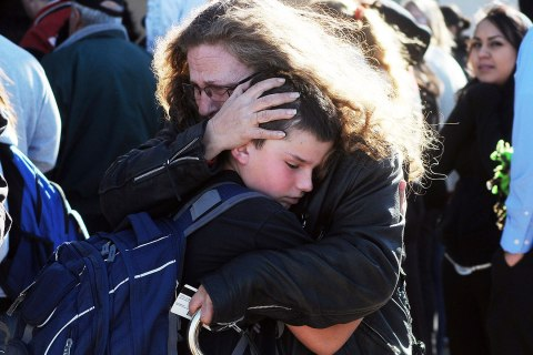 Students are reunited with families at a staging ground set up at the Roswell Mall following an early morning shooting at Berrendo Middle School in Roswell