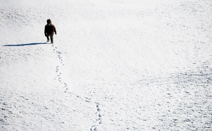 A boy walks across the snow covered lawn in front of the Capitol Visitor Center at the U.S. Capitol in Washington, Jan. 3, 2014.
