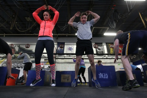 Maureen Becker and Dan Dougherty do burpees during a warm-up in a class at Crossfit New England, in Natick, Mass.