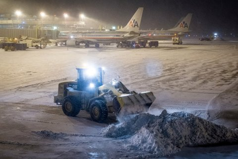 Crews work to remove the snow from the tarmac at Reagan National Airport in Washington, Jan. 21, 2014, after winter storm socked in the Mid-Atlantic region.
