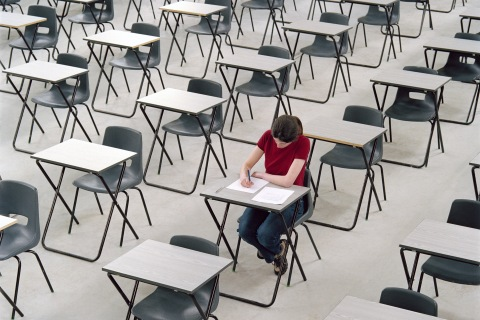 Young woman taking an exam at her desk.
