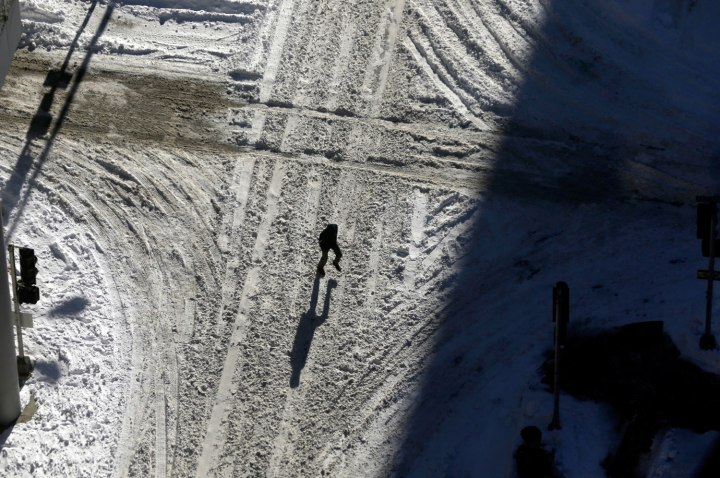 A person crosses a snow-covered street Monday, Jan. 6, 2014, in St. Louis.