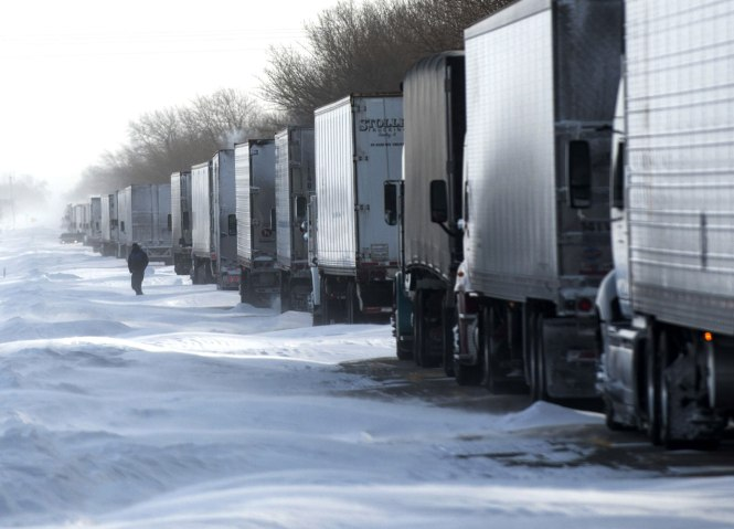 A trucker ventures out of his truck, stranded in a line of semi trucks in the eastbound lane of U.S 150 on Jan. 6, 2014.