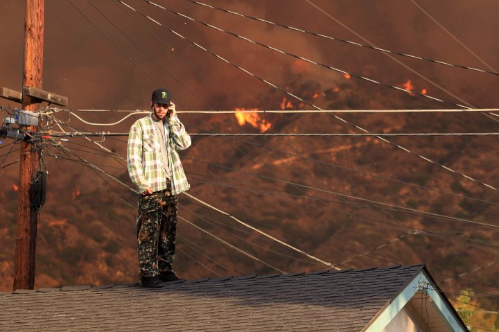 A resident on the roof of a house talks on the phone as a wildfire burns in the hills just north of the San Gabriel Valley community of Glendora, Calif., Jan 16, 2014.