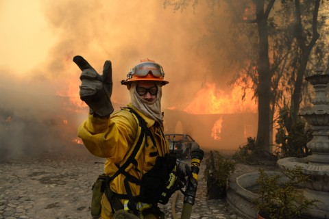 A fireman calls for more water on the burning Singer home above Glendora, Calif., Jan. 16, 2014.