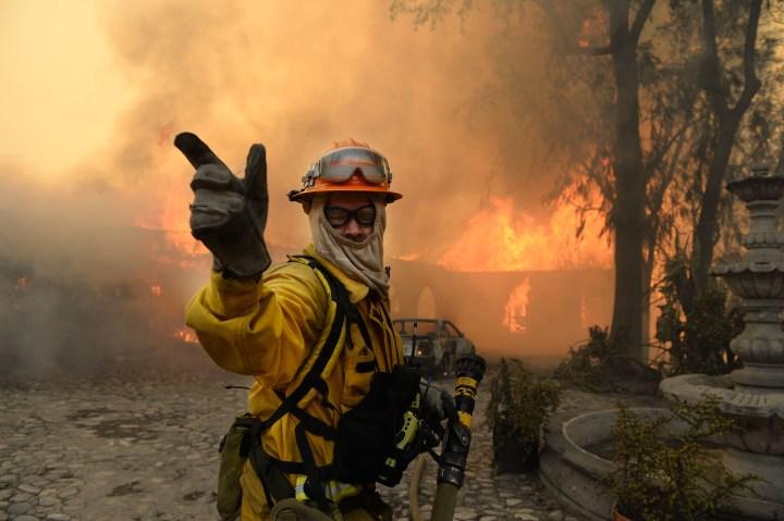 A fireman calls for more water on the burning Singer home above Glendora, Calif., Jan. 16, 2014.