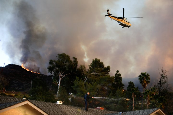 A helicopter carrying water flies over the residential area as a man sprays water on his home in Azusa, Calif., Jan. 16, 2014.