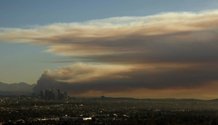 A large plume of smoke rises above the downtown Los Angeles skyline from the fast-growing Colby fire, January 16, 2014.