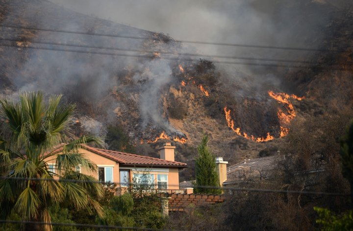 Flames burn near a home during tahe Colby Fire, January 16, 2014 in Azusa, Calif.