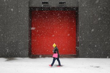 A woman walks outside of an office building as snow falls, Jan. 21, 2014, in Baltimore.