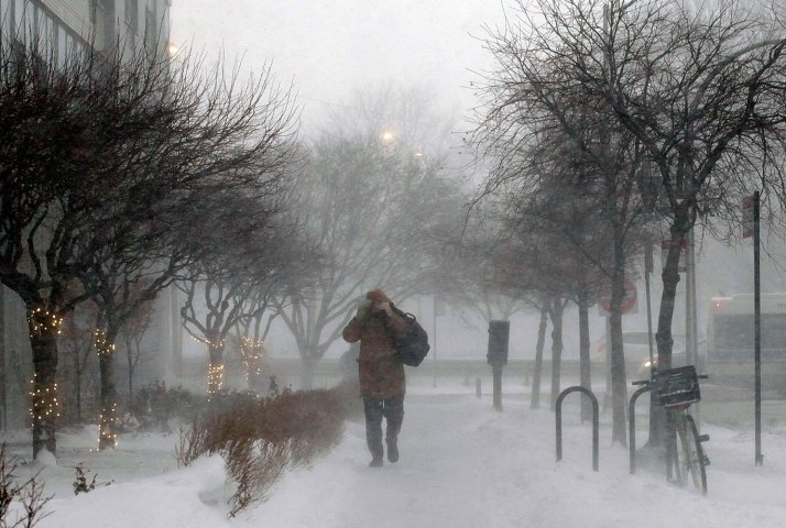 A morning commuter walks against blowing snow in Chicago.