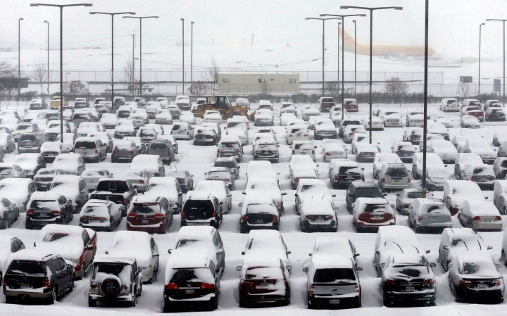 Cars are covered by snow in a parking lot at O'Hare International Airport in Chicago, Jan. 2, 2014.