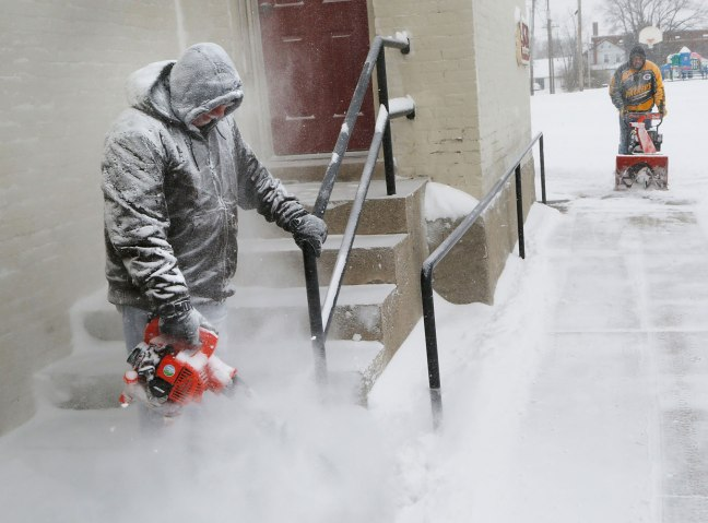 Tim Johnson, left, and Michael Bennett clear the snow from the sidewalks and steps around St. James Lutheran Church in Lafayette, Ind., Jan. 2, 2014.