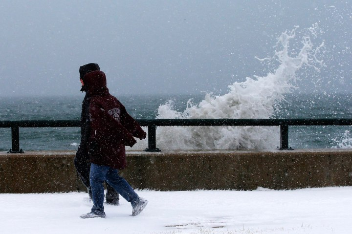 Onlookers walk past waves crashing against the seawall around high tide during a winter nor'easter snow storm in Lynn