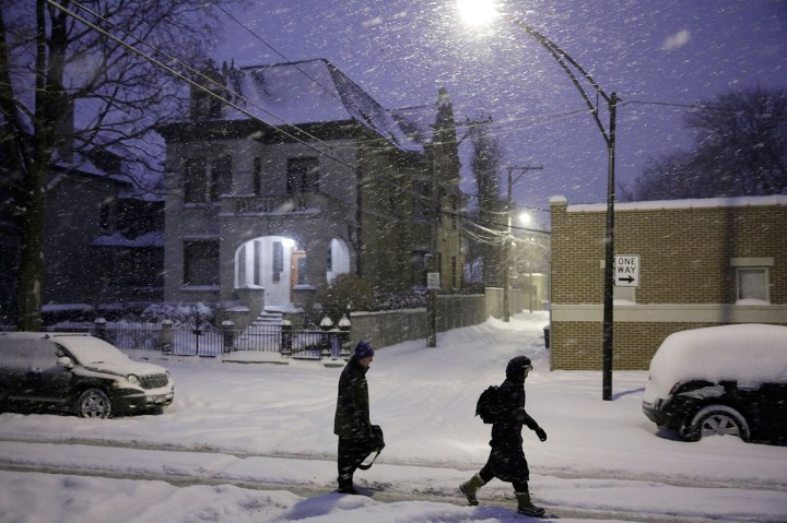 Commuters take to the middle of the street on Pierce Avenue in Wicker Park as snow continues to fall in Chicago, Jan. 2, 2014.