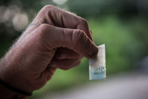 "A man holds a bag of heroin labeled ""Crazy Horse"" in Camden, N.J., Aug. 21, 2013."