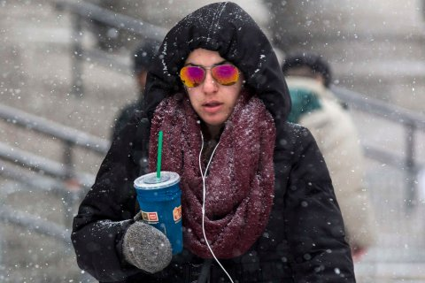 A woman walks through the blowing snow in the downtown area of New York