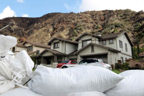 Sandbags line a residential street below recently burned hillsides in preparation against possible flash floods and mud slides in the second of two storms to hit drought-plagued California this week in Azusa, California