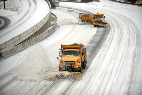 Snow plows clear downtown lanes on Interstate 75/85 during a winter storm on Feb. 12, 2014, in Atlanta.