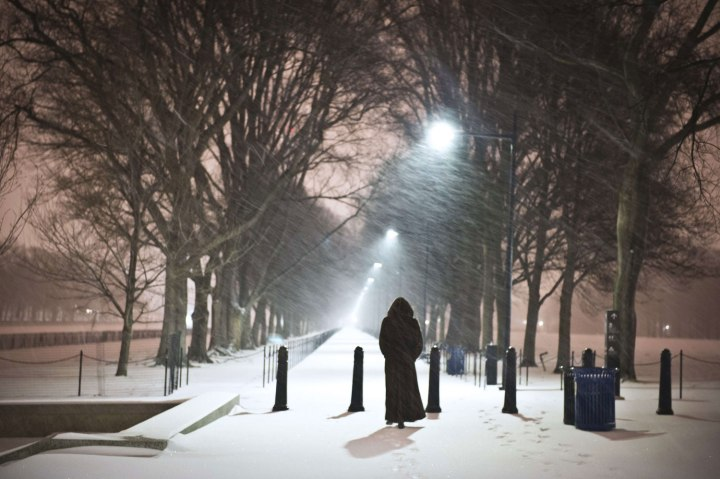 A woman walks next to the Reflecting Pool in front of the Lincoln Memorial as a heavy snow storm hits Washington D.C. on Feb. 13, 2014.